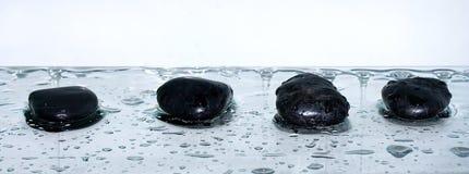 Four volcanic polished stones  zen. Four volcanic polished stones zen on wet blue Stock Photo