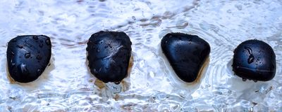Four volcanic polished stones in zen composition. On wet water drops marble surface Stock Image