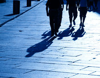 Four walking people shadows Royalty Free Stock Photos