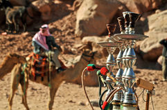 Four waterpipes and a beduin. Four water pipes waiting for the tourists, with a camel driver in the background. Petra, Jordan royalty free stock photo