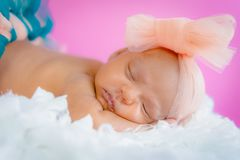 Four weeks baby infant girl studio photo sleeping on fluffy pillow wearing tutu and bow. Close up Stock Photo