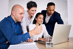 Four well dressed individuals working together on one notebook Royalty Free Stock Photo