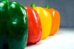 Four wet peppers closeup straight on. Four wet peppers (green, red, yellow, orange) in a row, level with the camera, closeup. Only red pepper is in focus Stock Images