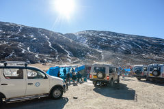Four wheel drive cars parking area with tourists and floating market with Yunthang Valley in the background in winter. Stock Images