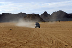 Four-wheel drive jeep on a desert road. In the Acacous Mountains, Sahara desert, Fezzan, Libya Royalty Free Stock Photo