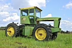 Four wheel drive John Deere tractor missing an engine. BARNESVILLE, MINNESOTA- June 2, 2014; An old four wheel drive John Deere is parked without an engine and Stock Photos