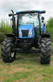 Four Wheel Drive Tractor. New blue and black four wheel drive tractor standing idle in a field Royalty Free Stock Image