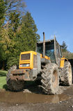 Four Wheel Drive Tractor. Standing idle on a driveway with a large puddle. Set against a clear blue sky with trees to one side Stock Images
