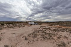 Four wheel drive vehicle  and large caravan parked in outback. Four wheel drive vehicle  and large caravan parked on an outback road under a cloudy sky Stock Image