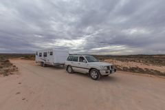 Four wheel drive vehicle  and large caravan parked on an outback track. Four wheel drive vehicle  and large caravan parked on an outback road under a cloudy sky Stock Photos