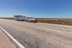 Four wheel drive vehicle and large caravan parked. By the side of the highway on the Nullarbor Plaine, Australia Royalty Free Stock Photo