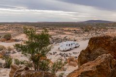 Four wheel drive vehicle and large white caravan camped. Beside ancient red cliffs in the outback of Australia Royalty Free Stock Image