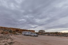 Four wheel drive vehicle and large white caravan. Camped beside ancient red cliffs in the outback of Australia Royalty Free Stock Photo