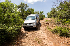 Four-wheel drive vehicle Mitsubishi Triton is doing off- road. Royalty Free Stock Photos