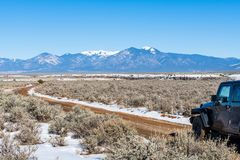 Four wheel drive vehicle on muddy dirt road curving towards snow-capped mountains stock photos