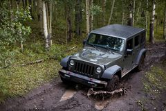 Four wheel drive vehicle splashing through mud. On a dirt track through a forest during an off-road adventure Stock Photos