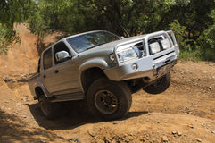 Four-wheel drive vehicle Toyota Hilux is doing off-road. Royalty Free Stock Photos