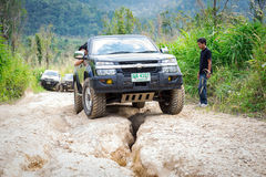 Four-wheel drive vehicles. Ratchaburi,Thailand -Dec 4,2016: Four-wheel drive vehicles were trying to go up the mountain road, which is rugged and steep Royalty Free Stock Image