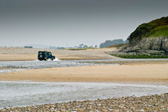 A four-wheel-drive in water between the sand dunes Royalty Free Stock Photography
