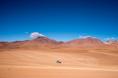 Four wheel drive (4WD) driving across the San Pedro de Atacama desert. A singe four wheel drive makes it's way across the San Pedro de Atacama desert on the way Royalty Free Stock Image