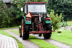 BIRMINGHAM, UK - March 2018 Four Wheeled Drive Mini Truck Hay Reaper in the Farm with Driver. Trees and Fruit Bearing royalty free stock photos