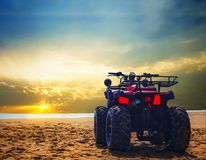 Four wheeler dirt bike on sand of sea beach during sunrise with dramatic colourful sky.  stock images