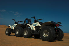 Four wheelers on the sand. A pair of four wheelers or ATVs in the sand Stock Images