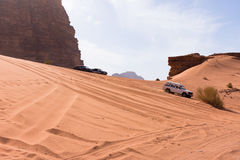 Four Wheeling in Wadi Rum. Down a large orange sand dune with rocky mountains in the background and blue sky with thin clouds above. Tire tracks are seen on the Stock Photography