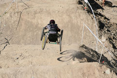 Four Wheels. A paraplegic racer flies down the hill on his custom made four wheeled bike Royalty Free Stock Photography
