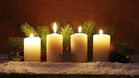 Four white Advent candles with christmas decoration. Christmas decoration with four candles for Advent . Four white candles in atmospheric light stock video footage
