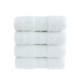 Four white bath towels in stack isolated over white Royalty Free Stock Photo