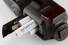 Four white batteries eneloop in flash canon isolated close up royalty free stock images