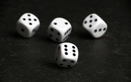 Four white and black dice on black table. Four white and black dice on a black table Stock Images