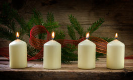 Four white burning candles  on the fourth advent, decorated with Royalty Free Stock Image