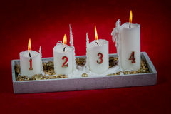 Four white burning candles welcoming fourth advent. Stock Image