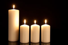 Four white candles on black Royalty Free Stock Photography