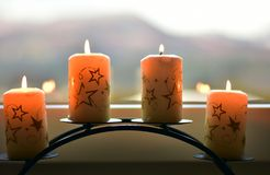 Four white candles with stars on the window sill. With blurred hills for the background Stock Photo