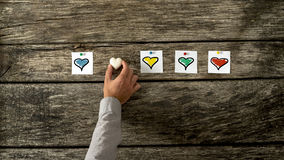 Four white cards with different coloured heart shapes on them pi. Nned in a row on textured wooden background with male hand placing stone made heart between Stock Image