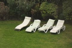 Chaise Lounges. Four white chaise lounges on the grass stock photography