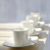 Four white cups. In a row Stock Photos