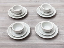 Four white cups and saucers on gray brown table Royalty Free Stock Photos