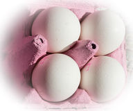 Four white eggs in pink carton Royalty Free Stock Images