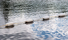 Four white floating marker buoys on water Royalty Free Stock Photo