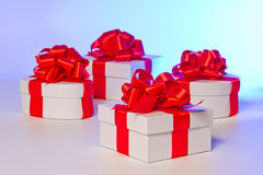 Four white gift boxes with red satin ribbon Royalty Free Stock Images