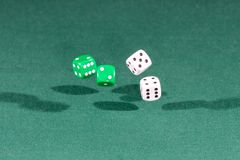 Four white and green dices falling on a green table. Four white and green dices falling on a isolated green table stock photo