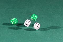 Four white and green dices falling on a green table. Four white and green dices falling on a isolated green table stock image