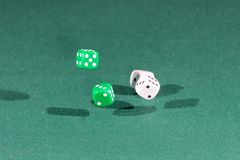 Four white and green dices falling on a green table. Four white and green dices falling on a isolated green table stock photography