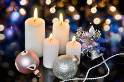 Four white lighted candles and Christmas decorations on a bokeh Royalty Free Stock Images