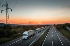 Four White Lorry Trucks Convoy on highway. At beautiful sunset royalty free stock photos