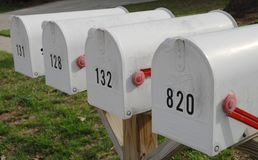 Four white mail boxes with red flags Stock Images